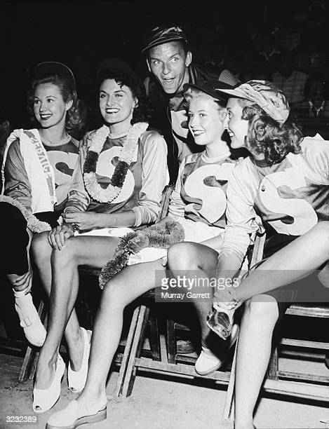 American singer and actor Frank Sinatra smiles as he poses behind his team 'The Sinatra Swooners' on the sidelines at a celebrity baseball game in...