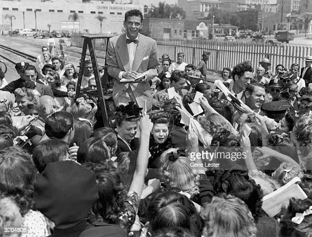 American singer and actor Frank Sinatra stands on a stepladder and signs autographs while fans surround him upon his arrival at a train station in...