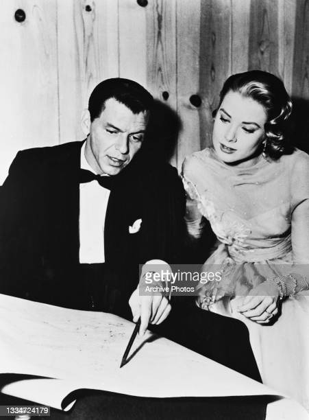 American singer and actor Frank Sinatra , wearing a tuxedo and pointing to a large document on a table, with American actress Grace Kelly in an...