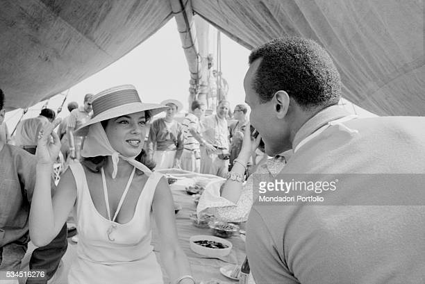 American singer and actor Harry Belafonte chatting with American singer and actress Abbe Lane during a boat trip. Venice, August 1958