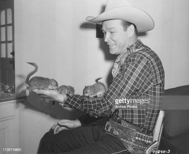 American singer and actor Roy Rogers with three orphan squirrels he came across during location filming for 'South of Caliente' 1951