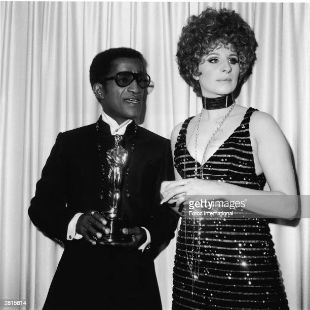 American singer and actor Sammy Davis Jr stands with presenter Barbra Streisand holding the Oscar for Best Song at the Academy Awards ceremony Santa...