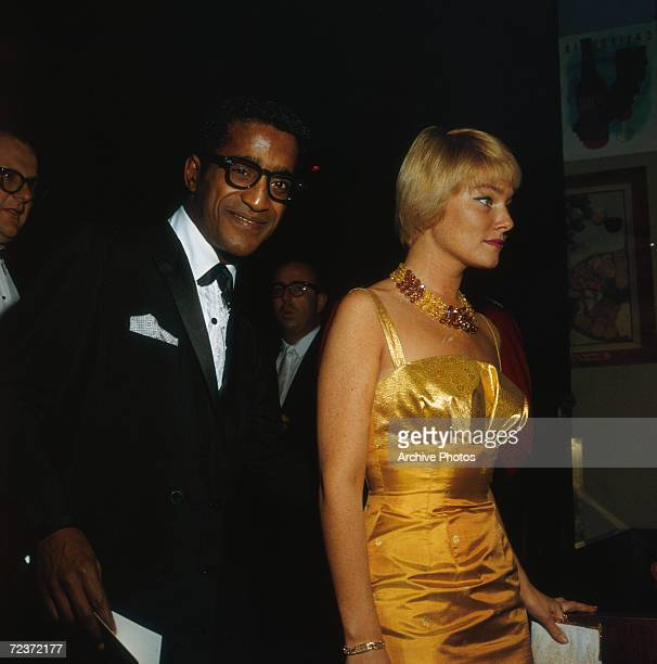American singer and actor Sammy Davis Jr wearing a tuxedo and his fiancee Swedish actress May Britt wearing a gold evening gown to the Thalians Ball...