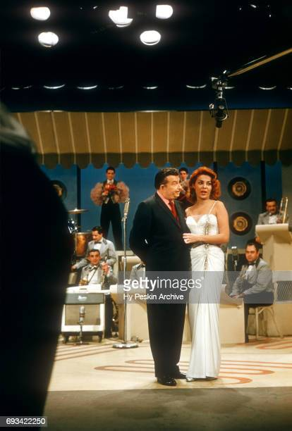 American singer and actress Abbe Lane and husband Xavier Cugat talk to the television audience as band members wait to play on April 23 1957