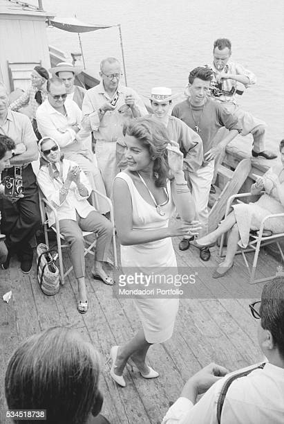 American singer and actress Abbe Lane dancing during a boat trip. Venice, August 1958