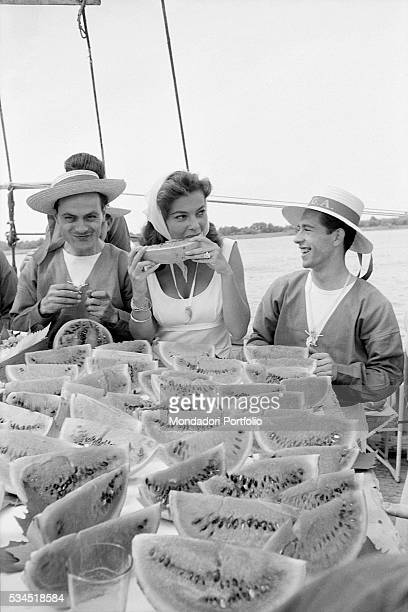 American singer and actress Abbe Lane eating watermelon during a boat trip. Venice, August 1958