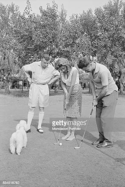 American singer and actress Abbe Lane playing golf in front of her husband and Spanish musician Xavier Cugat at the 19th Venice International Film...