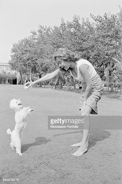 American singer and actress Abbe Lane playing with her dog at the 19th Venice International Film Festival. Venice, August 1958
