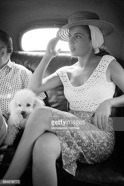 American singer and actress Abbe Lane sitting in her car with her dog at the 19th Venice International Film Festival. Venice, August 1958