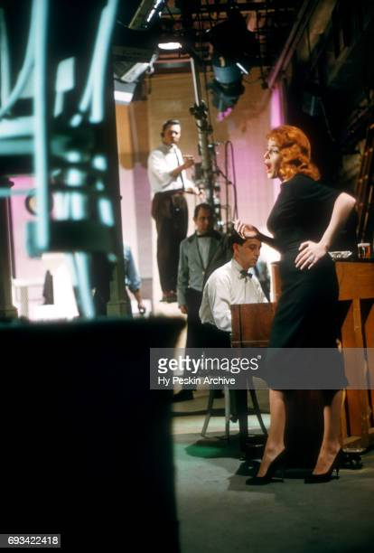 American singer and actress Abbe Lane smokes as she performs on stage on April 23 1957