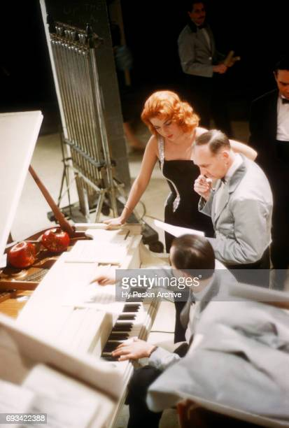 American singer and actress Abbe Lane talks to a band member about the music before she goes on stage to perform on April 23 1957