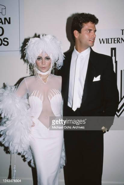 American singer and actress Apollonia Kotero wearing a white dress and matching headdress both decorated with white feathers and American actor...