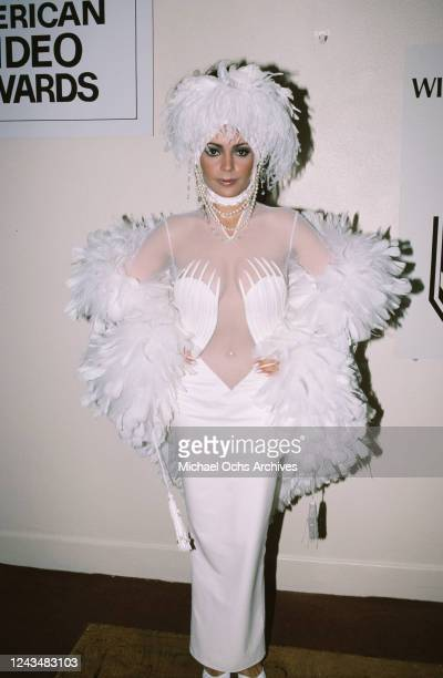 American singer and actress Apollonia Kotero wearing a white dress and matching headdress both decorated with white feathers attends the 4th Annual...