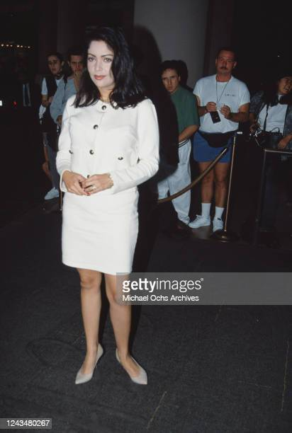 American singer and actress Apollonia Kotero wearing a white suit with large metal buttons on the chest standing in front of a cordon beyond which...
