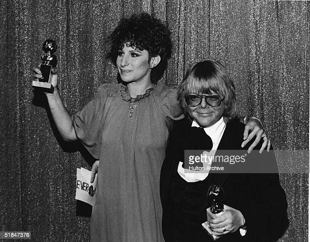 American singer and actress Barbra Streisand and American composer and actor Paul Williams hold their Golden Globe awards for Best Original Song...
