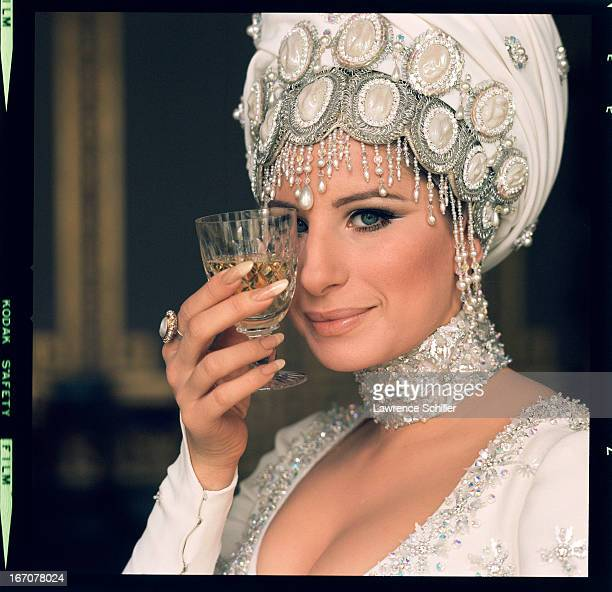 American singer and actress Barbra Streisand holds a wine glass up to her eye during the filming of 'On a Clear Day You Can See Forever' Brighton...