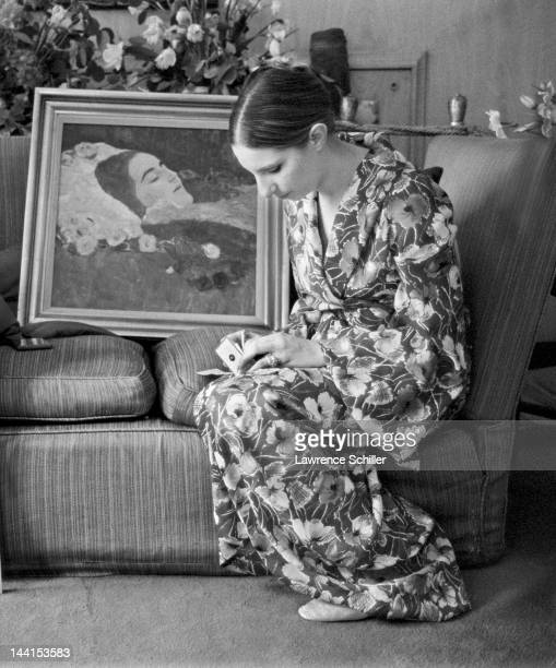 American singer and actress Barbra Streisand in a flowered robe sits on a sofa and writes a check for the purchase of a painting by Gustav Klimt in...