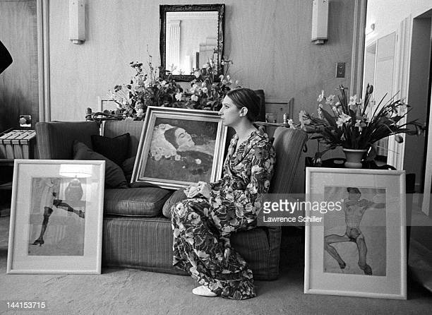 American singer and actress Barbra Streisand in a flowered robe sits on a sofa and writes a check for the purchase of a painting by Gustav Klimt and...