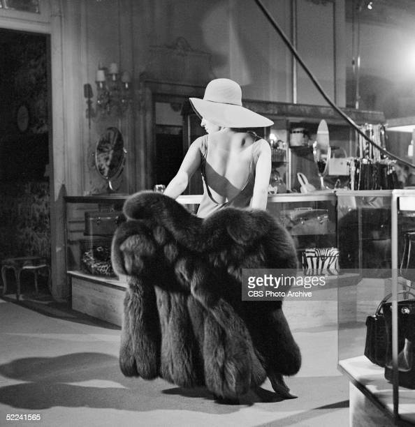 American singer and actress Barbra Streisand tries on a fur coat as she tapes a scene inside the Fifth Avenue department store Bergdorf Goodman for...