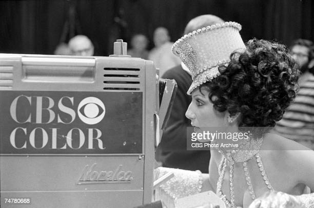 American singer and actress Cher dress in a lowcut sequined costume and matching cap looks through a CBS television camera during the filming of an...