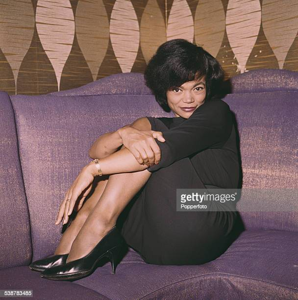 American singer and actress Eartha Kitt pictured wearing a black dress and sitting on a couch in 1962