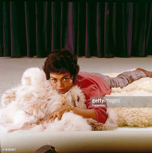 American singer and actress Eartha Kitt posed lying on a fur rug in 1965