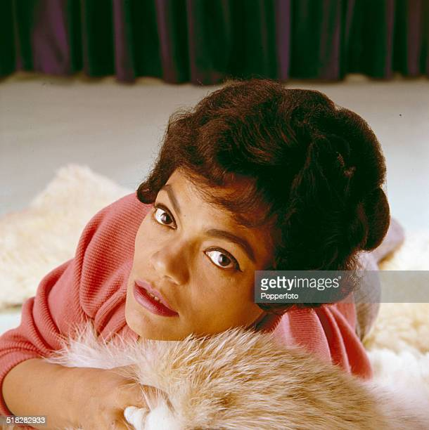American singer and actress Eartha Kitt posed on a fur rug in 1965
