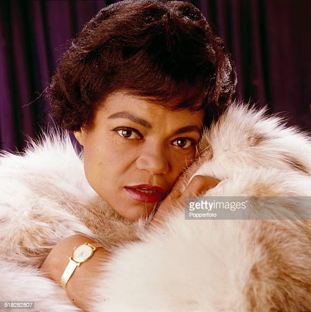 American singer and actress Eartha Kitt posed wrapped in a fur rug in 1965