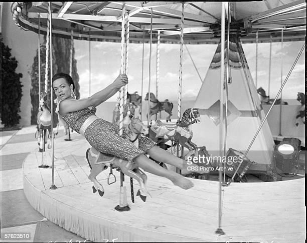 American singer and actress Eartha Kitt sits on a carousel horse as she performs on Ed Sullivan's CBS variety show 'Toast of the Town' New York...