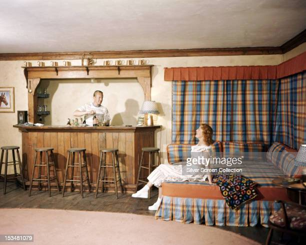 American singer and actress Jeanette MacDonald sits on a bed while her husband American actor Gene Raymond acts as bartender circa 1950