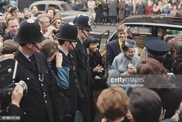 American singer and actress Judy Garland and best man Johnnie Ray leave their car on the King's Road to walk past crowds of onlookers and police...