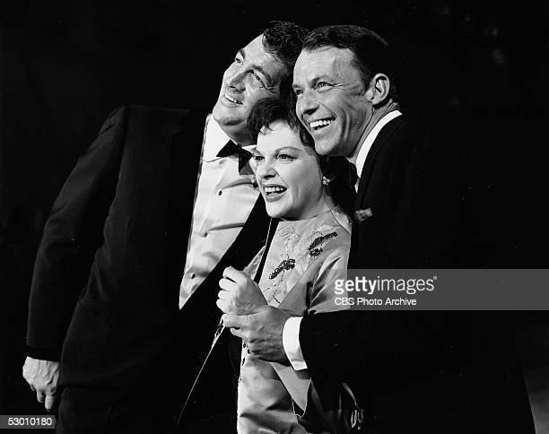 American singer and actress Judy Garland is flanked by American singers and actors Dean Martin and Frank Sinatra in a still from the famed television...