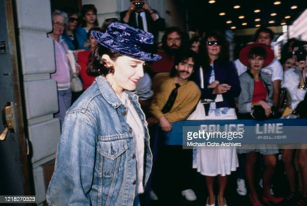 American singer and actress Madonna wearing a purple velvet hat as she leaves a theatre on Broadway, New York City, circa 1988.