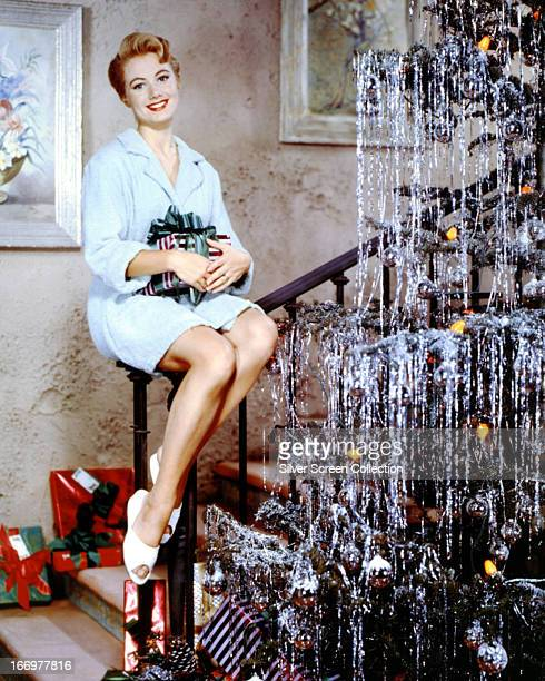 American singer and actress Shirley Jones sitting beside a Christmas tree circa 1960