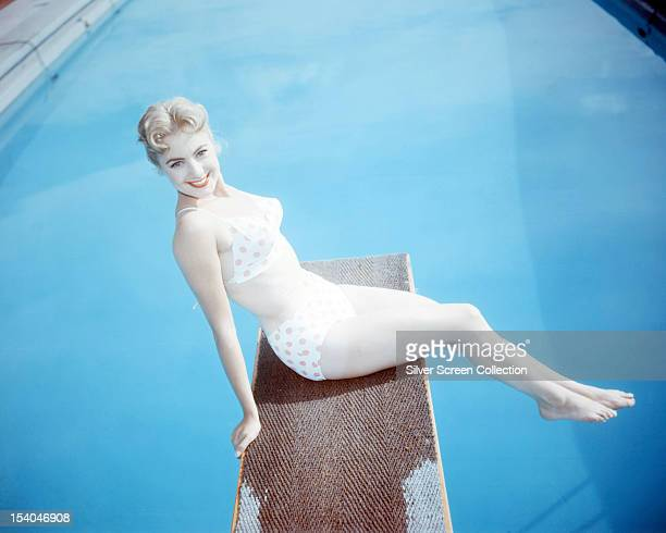 American singer and actress Shirley Jones sitting on a diving board in a red and white polkadot bikini circa 1955