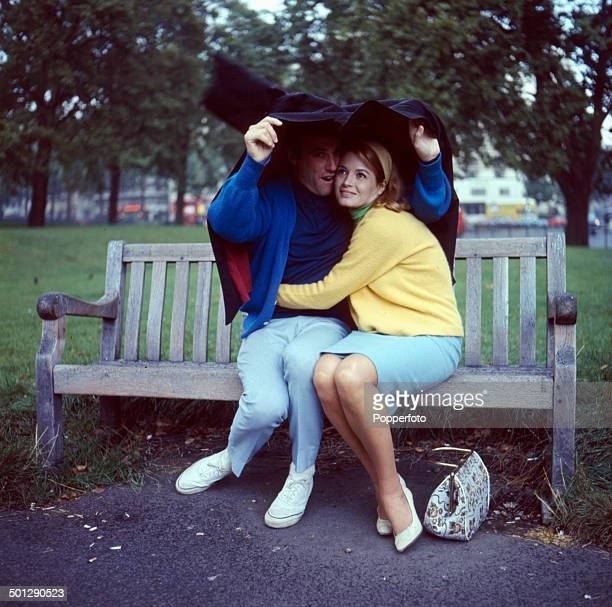 American singer and composer Burt Bacharach and his wife actress Angie Dickinson shelter from the rain in a London park in 1966
