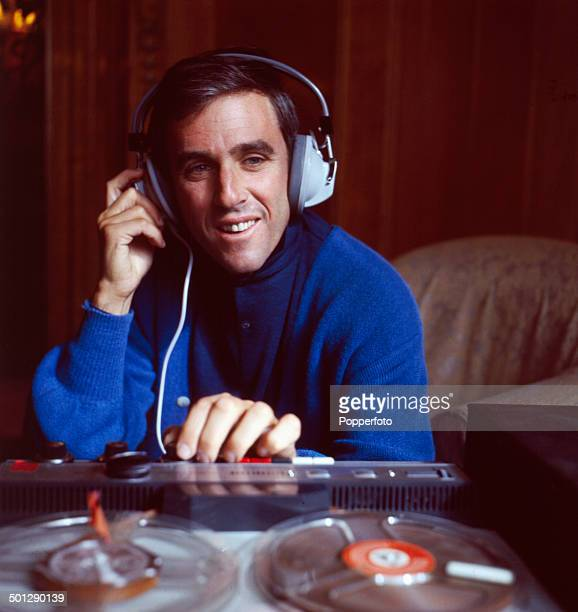 American singer and composer Burt Bacharach listens to a recording from a reel to reel tape recorder through headphones in London in 1966