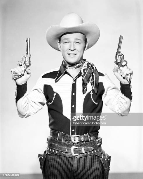 American singer and cowboy actor Roy Rogers holding a pair of pistols circa 1940