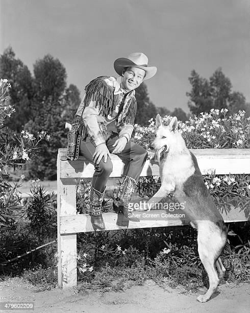 American singer and cowboy actor Roy Rogers with a German Shepherd dog circa 1945