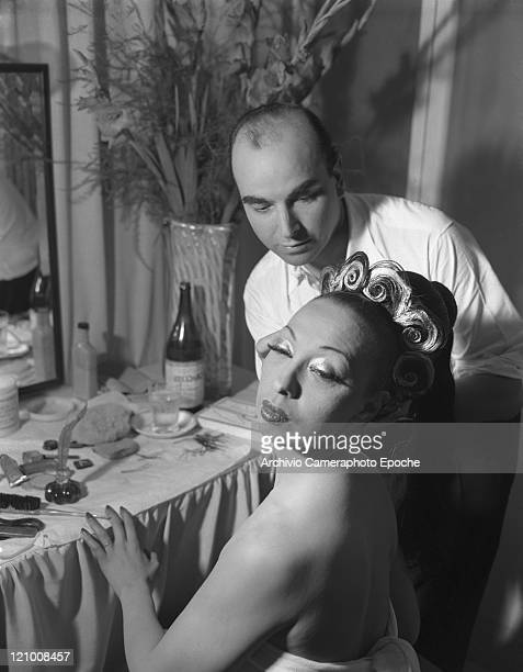 American singer and dancer Josephine Baker portrayed in front of her dressing room mirror while maked up by Jean Clement Venice 1949
