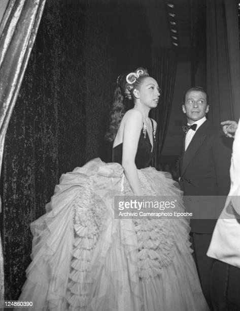 American singer and dancer Josephine Baker wearing a tulle evening dress standing outside the stage Venice 1949