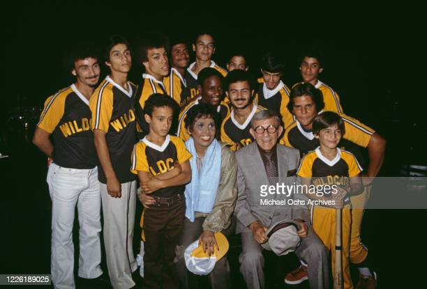American singer and dancer Lena Horne with American comedian George Burns and players of Horne's baseball team in New York City, New York, 4th...