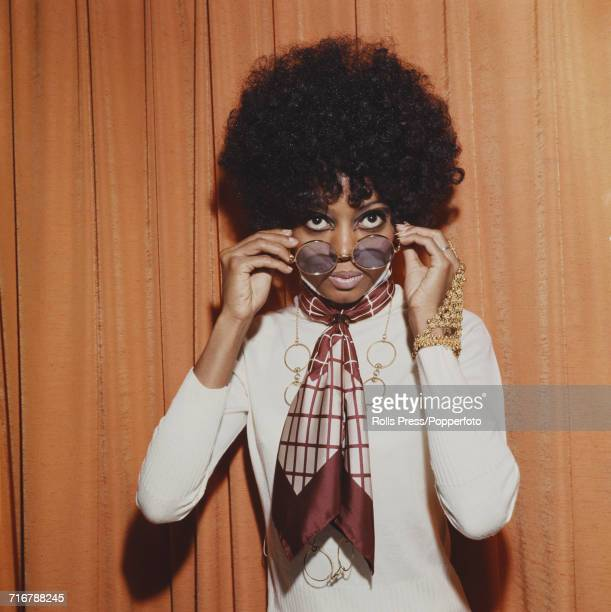American singer and lead singer of The Supremes Diana Ross pictured wearing a neck scarf and holding a pair of metal rimmed sunglasses in London in...