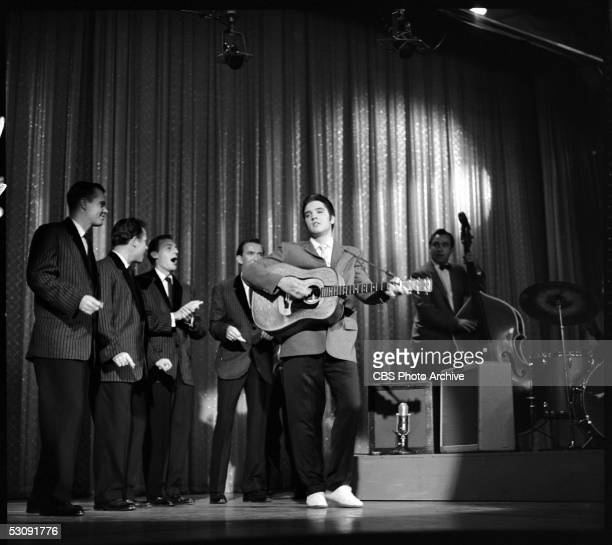 American singer and musician Elvis Presley performs with his band onstage during his second appearance on 'The Ed Sullivan Show,' New York, New York,...