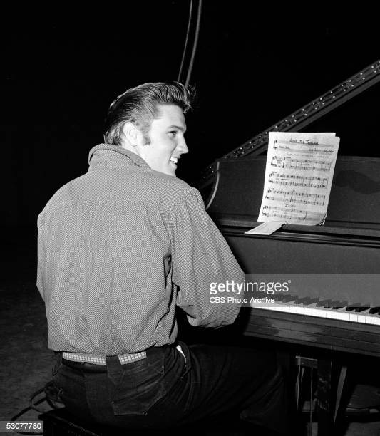American singer and musician Elvis Presley sits at a piano with sheet music for 'Love Me Tender' while in the studio to perform on 'The Ed Sullivan...