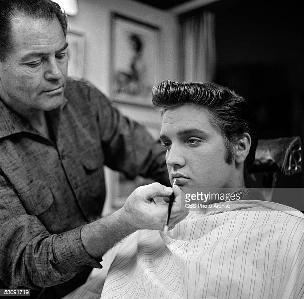 American singer and musician Elvis Presley sits in a chair as a makeup artist highlights his lips backstage at 'The Ed Sullivan Show' Los Angeles...