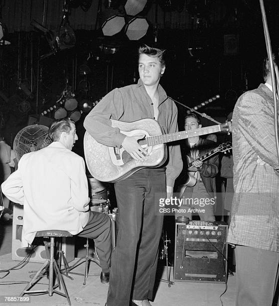 American singer and musician Elvis Presley stands backstage on 'The Ed Sullivan Show' while members of his band rehearse behind him, Los Angeles,...