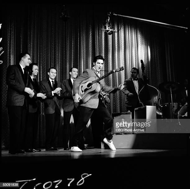 American singer and musician Elvis Presley swivels his hips as he performs with his band onstage during his second appearance on 'The Ed Sullivan...