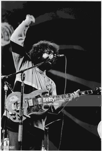 American singer and musician Jerry Garcia lead guitarist and vocalist of the psychedelic rock band the 'Grateful Dead' lifts up a clenched fist as he...
