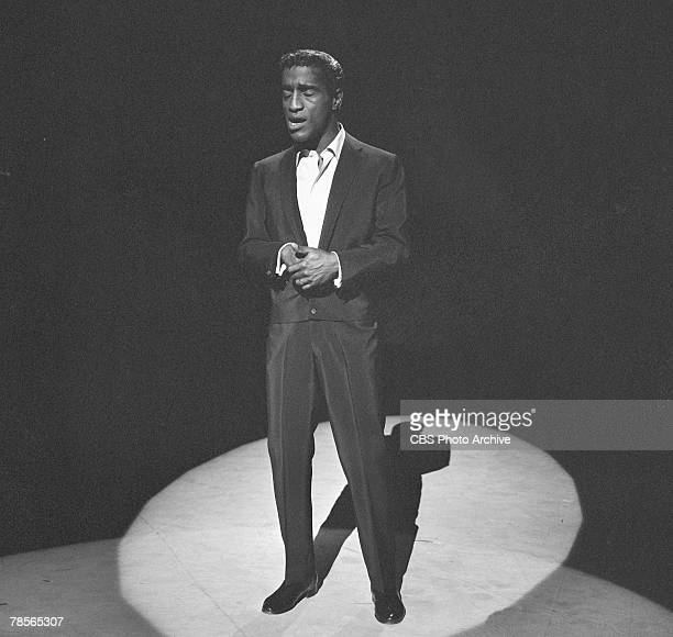 American singer and musician Sammy Davis Jr sings in the spotlight on an episode of 'The Big Record' April 9 1958